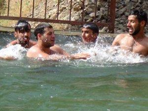 Hakkarili çiftçiler sulama havuzunda serinliyor